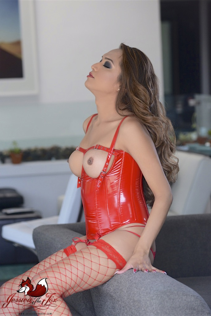 Jessica is super hot in red latex while she jerks her dick off.